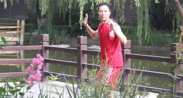 Человек занимается Тайцзицюань в Пекине на берегу реки